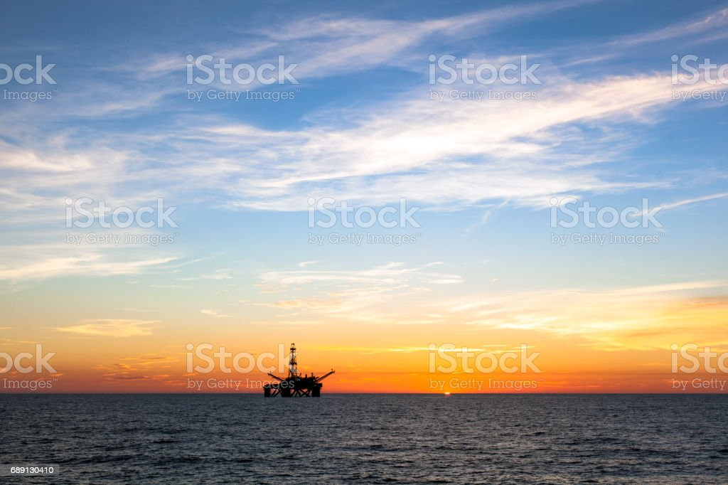 Silhouette of offshore oil platform at sunset stock photo