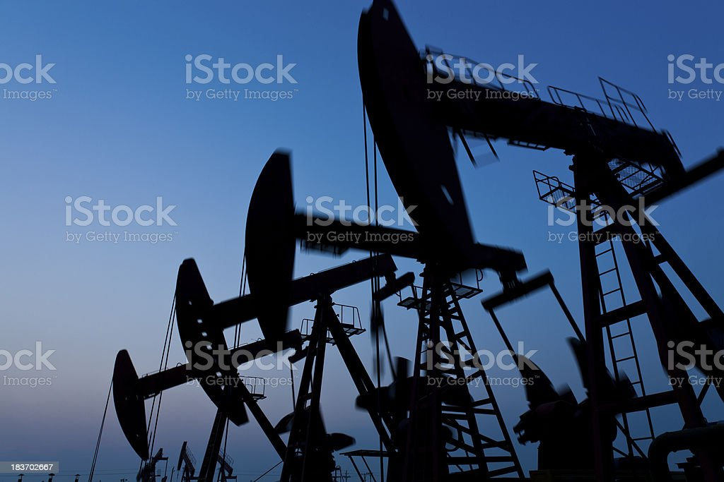 Silhouette of oil pump jack stock photo