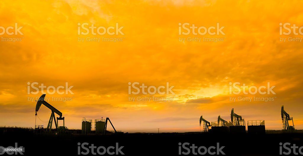 Silhouette of Oil pumps at oil field stock photo