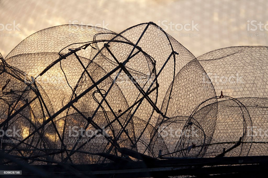Silhouette of old fishing nets against sunrise sky stock photo