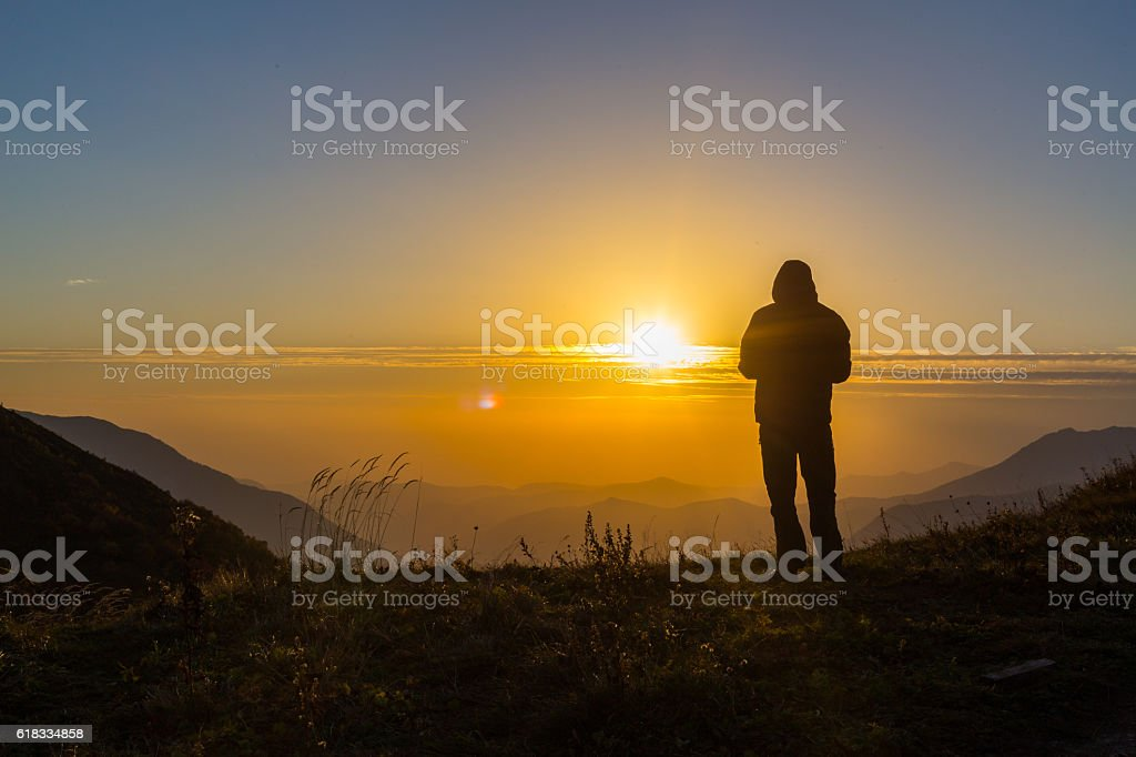 Silhouette of one young man standing at the mountains top stock photo