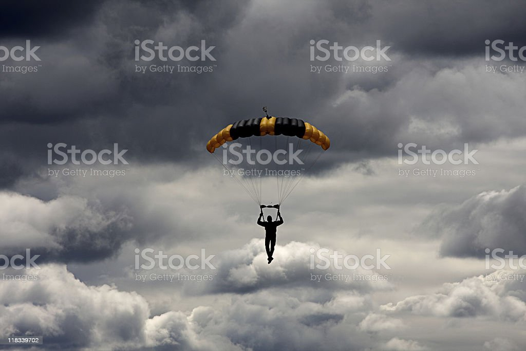 Silhouette of paratrooper in stormy sky stock photo