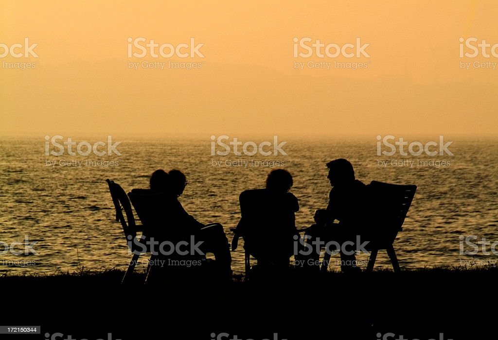 A silhouette of people at the beach stock photo