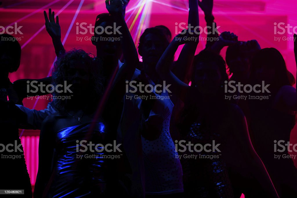 Silhouette of people dancing in club with pink laser royalty-free stock photo