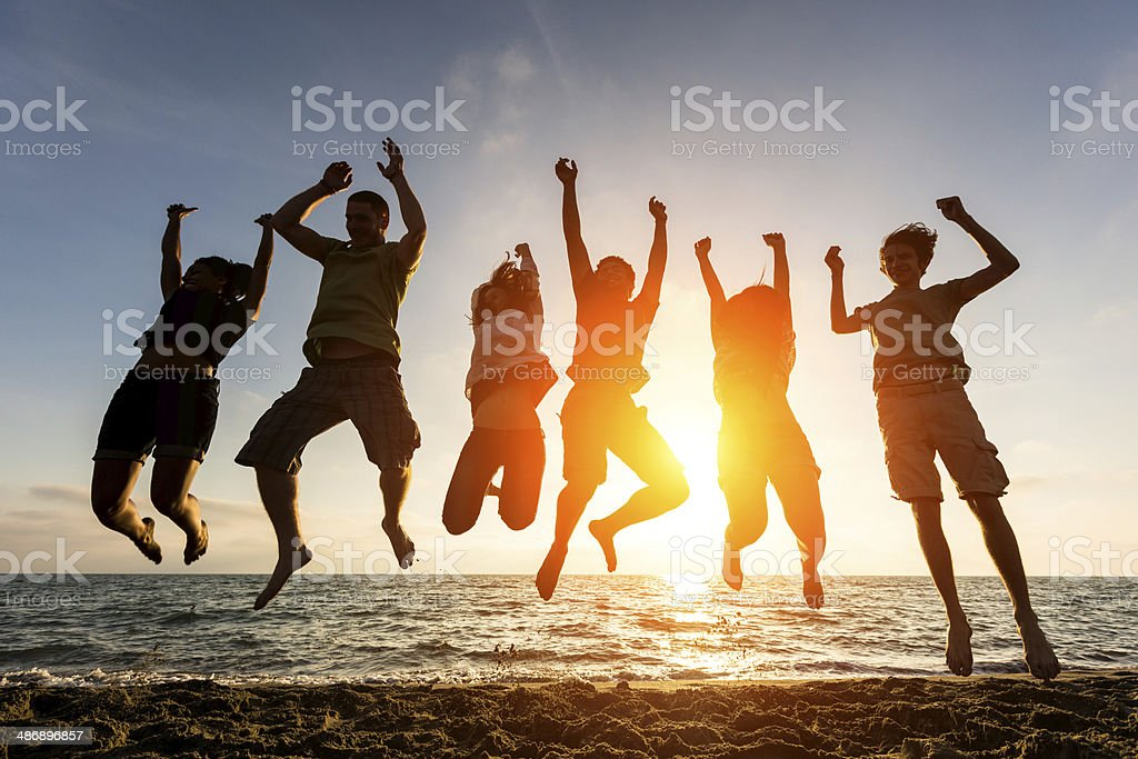 Silhouette of people jumping at a beach stock photo