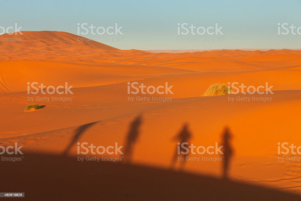 Silhouette of people on dunes in desert stock photo