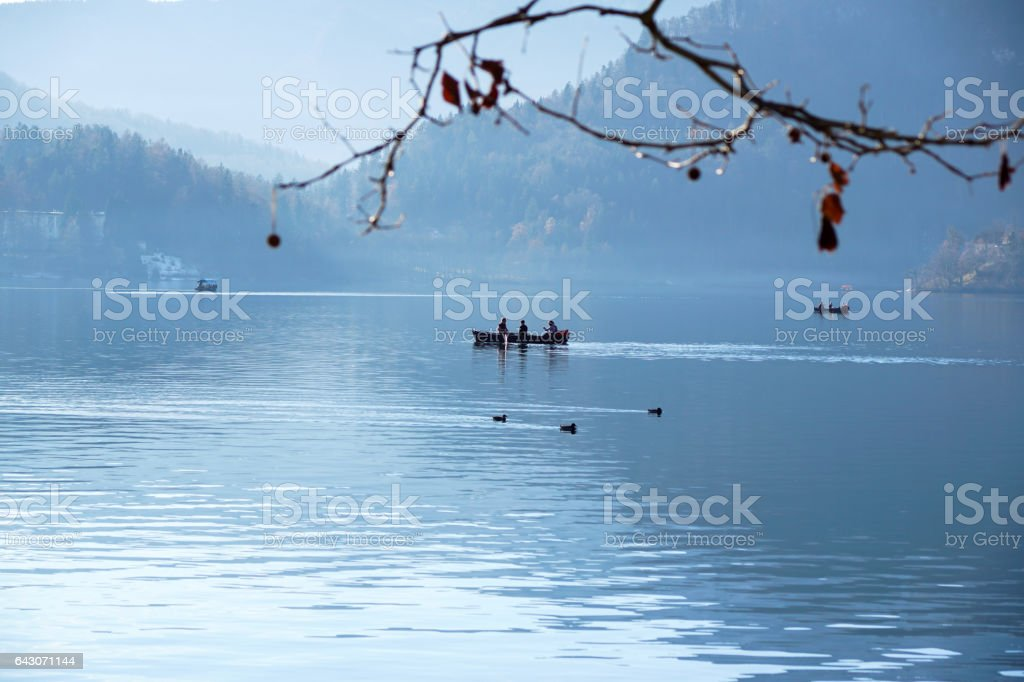 silhouette of people rowing a boat in the river at lake stock photo
