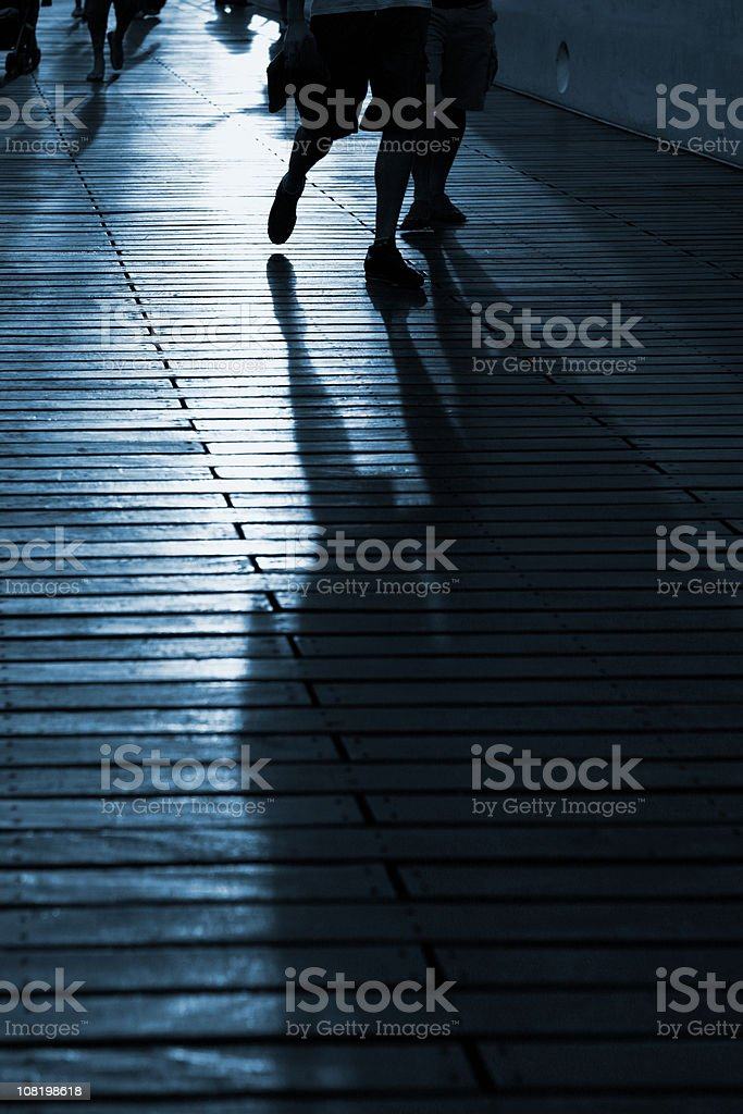 Silhouette of People Walking Down Bridge royalty-free stock photo