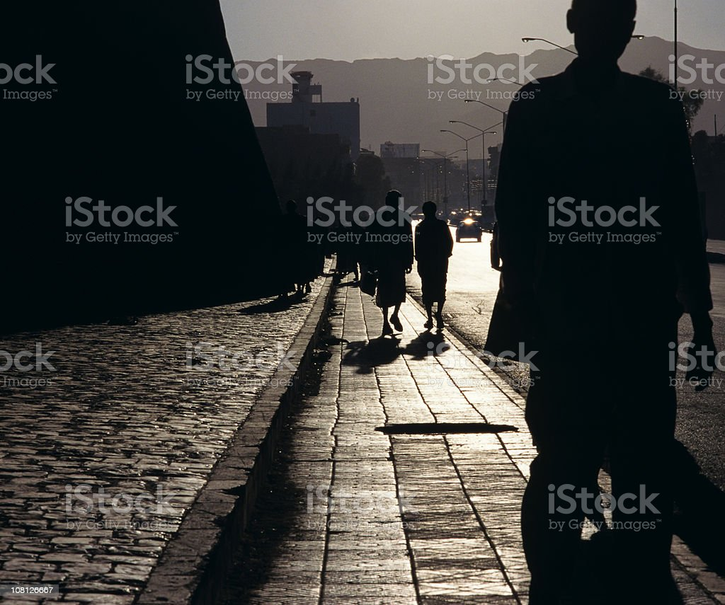 Silhouette of People Walking Down Sidewalk stock photo