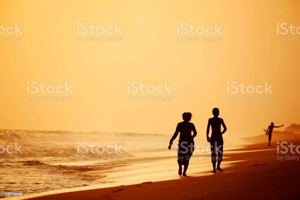 Silhouette of people walking on beach at sunset royalty-free stock photo