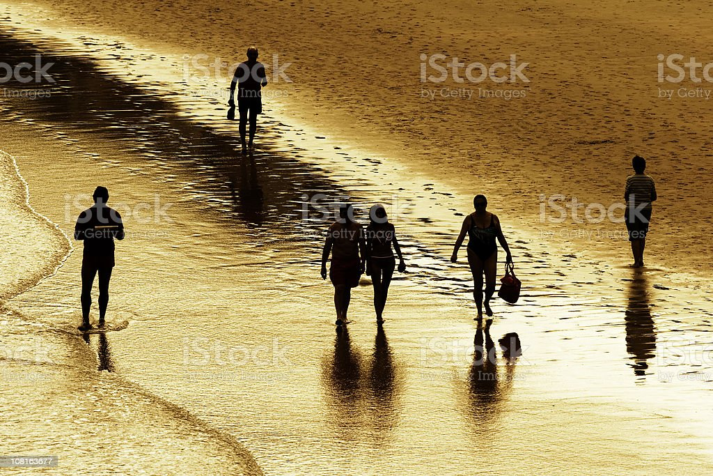 Silhouette of people Walking Through Beach stock photo