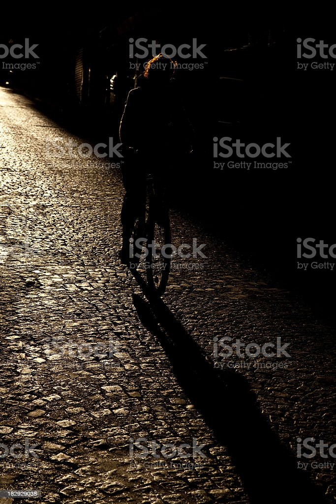 Silhouette of Person Riding Bicycle on Cobbled Street in Paris royalty-free stock photo