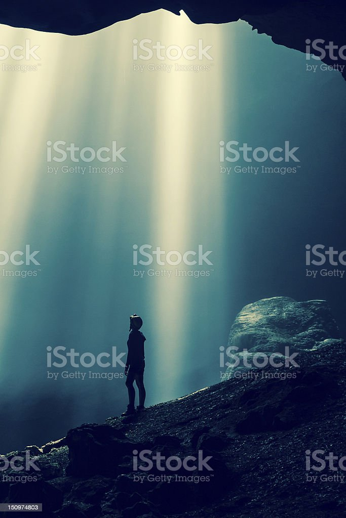 Silhouette of person standing in cave royalty-free stock photo