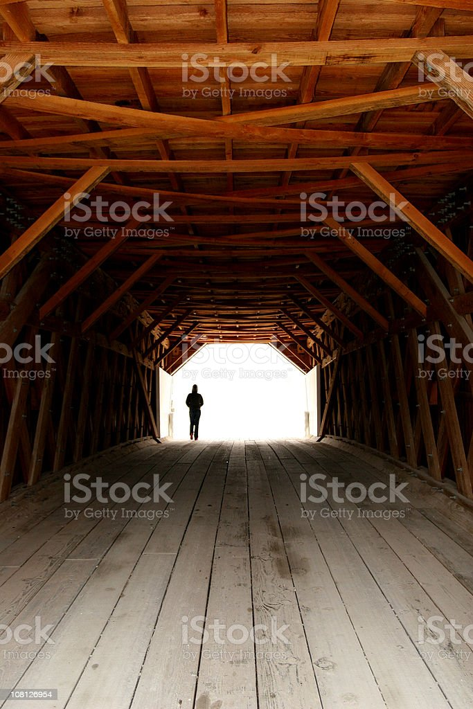 Silhouette of Person Walking Down Wooden Covered Bridge stock photo