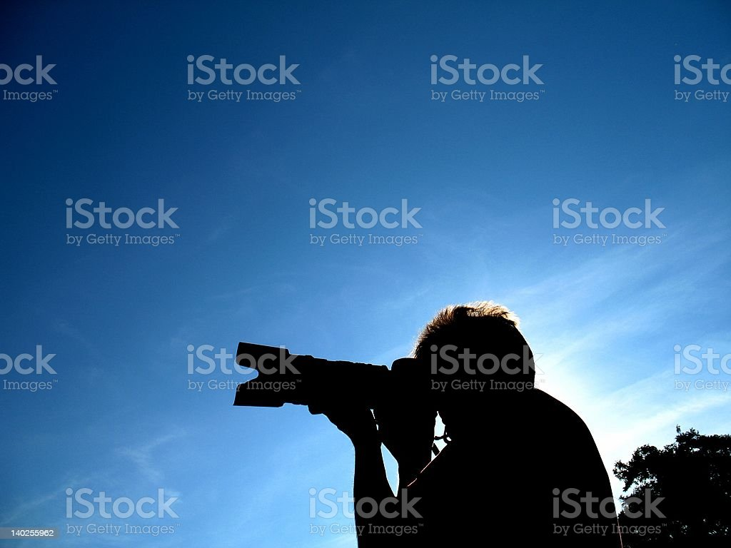 Silhouette of photographer at work stock photo