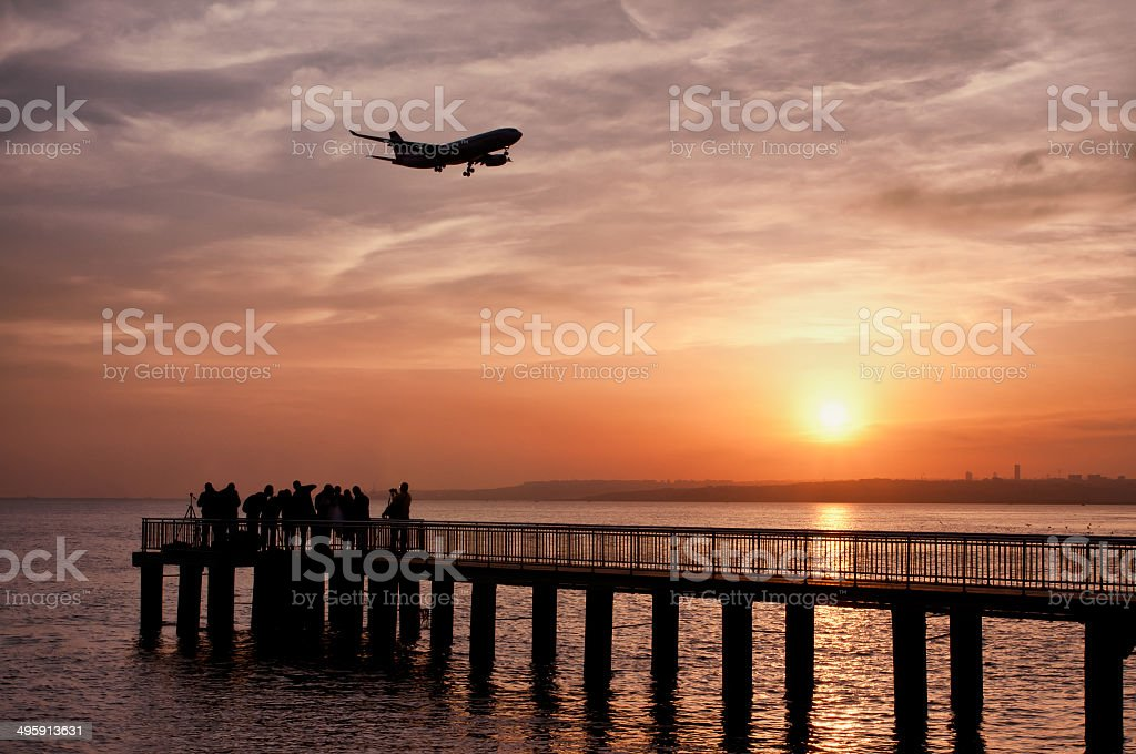 Silhouette of photographer group on pier and plane stock photo