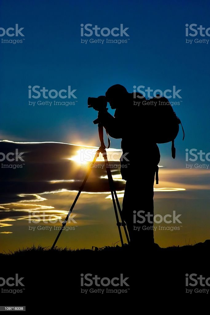Silhouette of Photographer Man and Camera Tripod at Sunrise stock photo