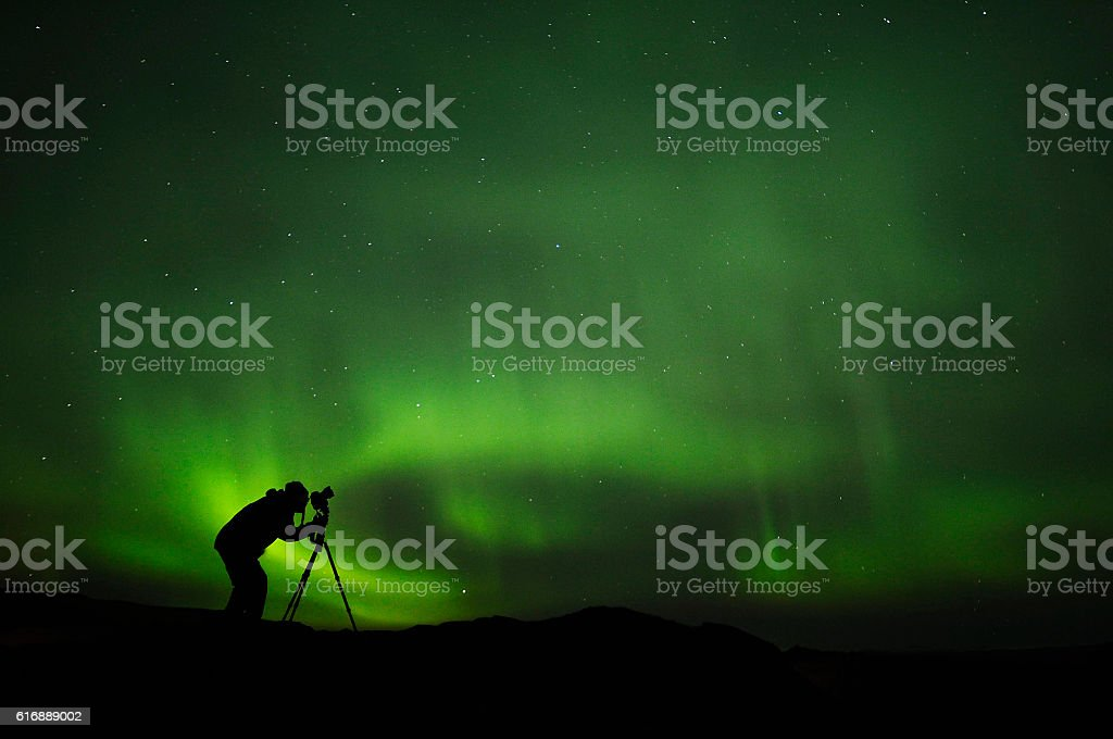 silhouette of photographer shooting aurora stock photo