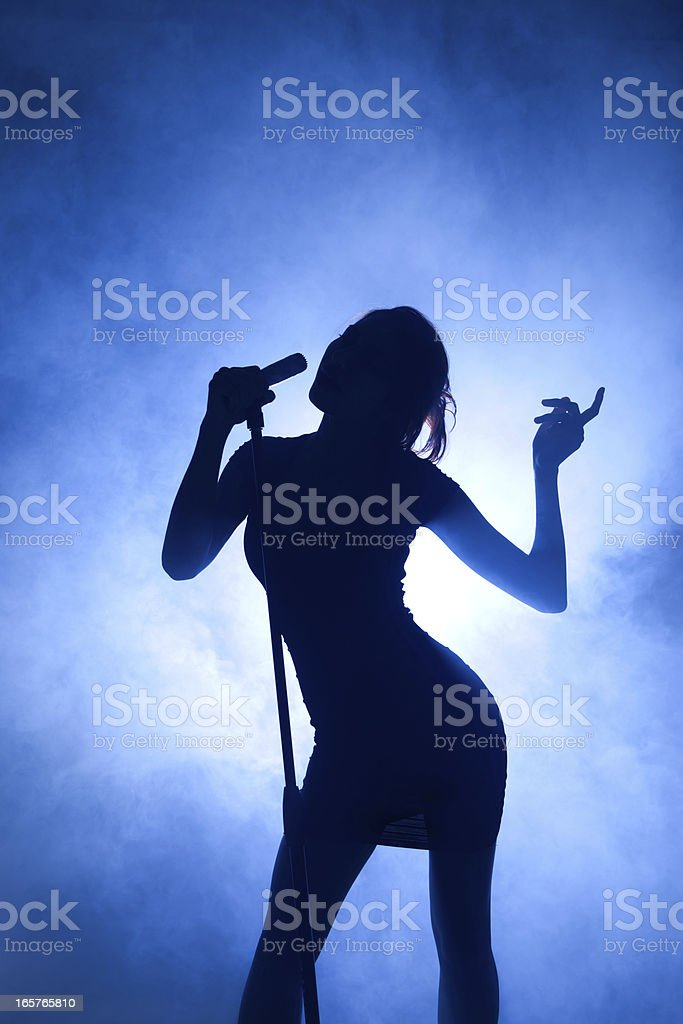 Silhouette of pop idol with microphone on blue background stock photo