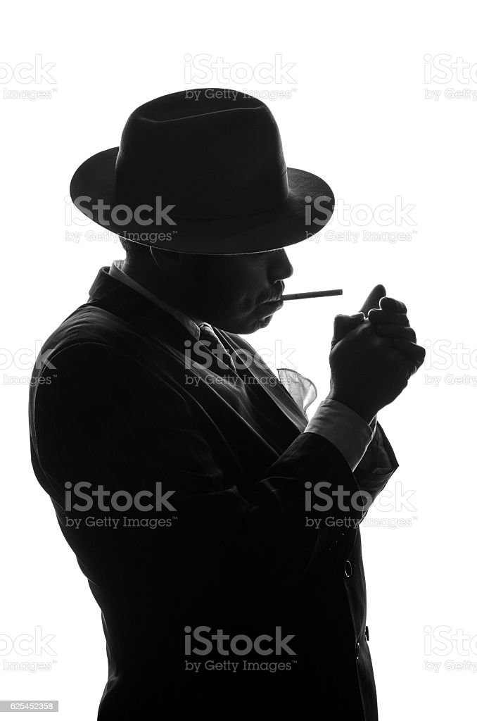 Silhouette of private detective lights cigarette. Agent looks like Al stock photo