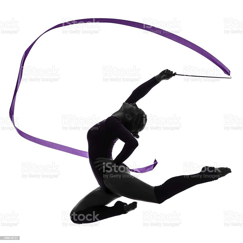 Silhouette of rhythmic gymnast leaping in air with ribbon stock photo
