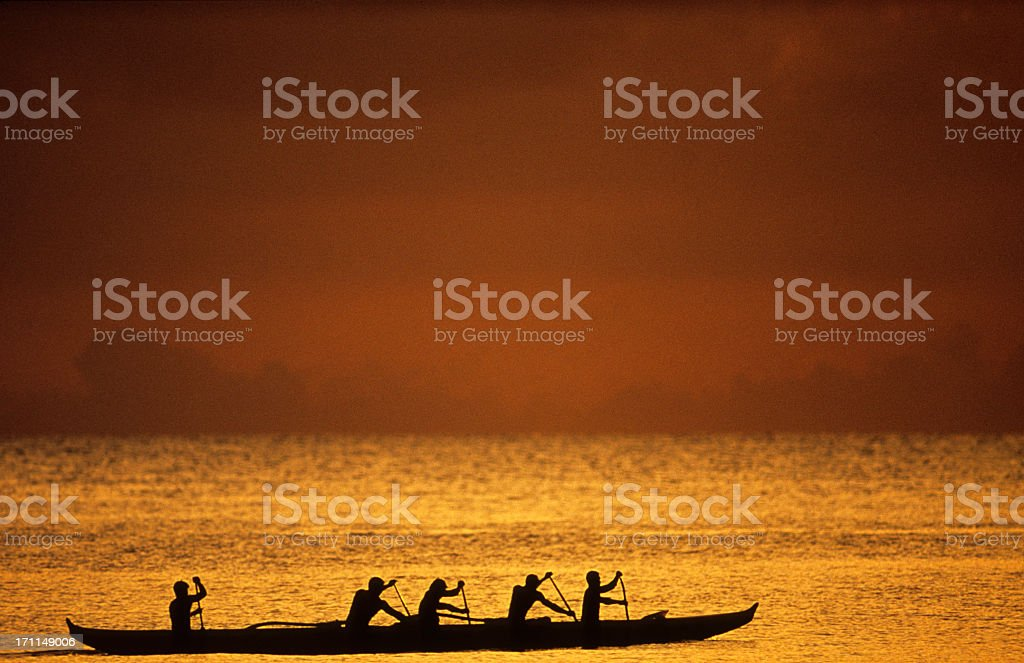 Silhouette of rowers at sunset in Oahu, Hawaii's North Shore stock photo