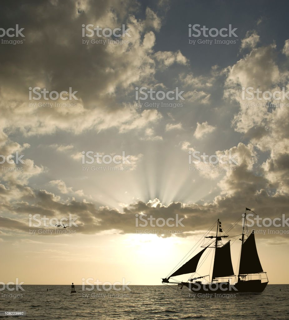 Silhouette of Sailboat on Horizon at Sunset royalty-free stock photo