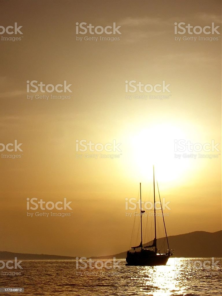 Silhouette of sailing boat in golden sunset stock photo