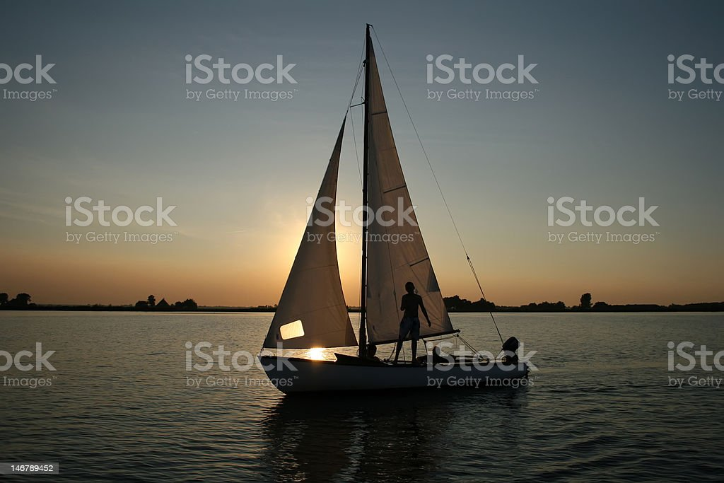 silhouette of sailing boat in the setting sun royalty-free stock photo