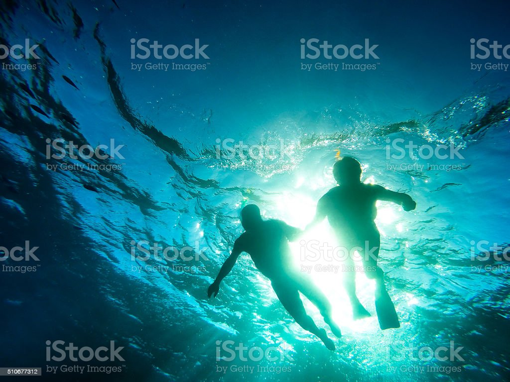 Silhouette of senior couple swimming together in tropical sea stock photo