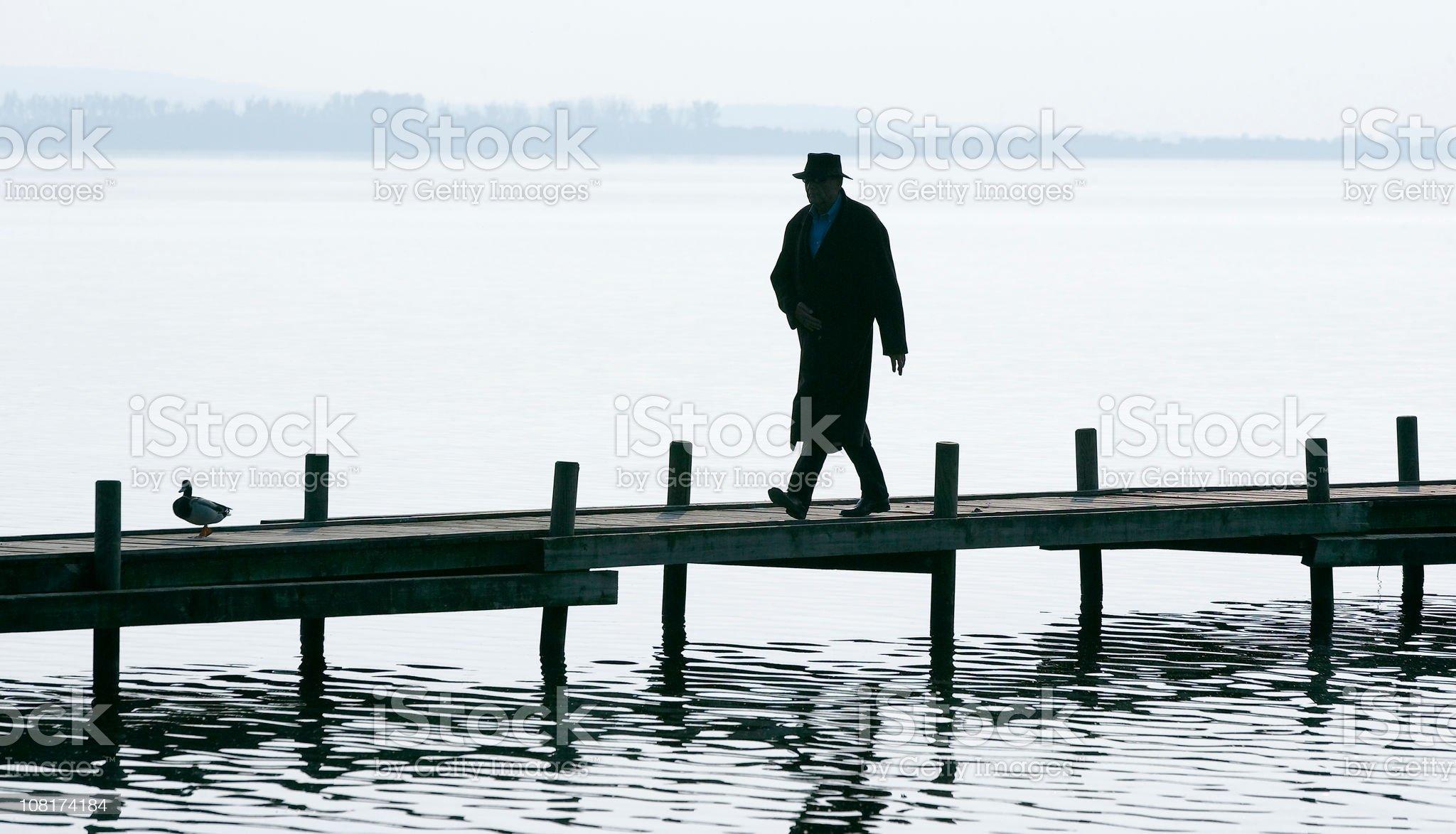 Silhouette of Senior man walking on Lakeside Jetty royalty-free stock photo