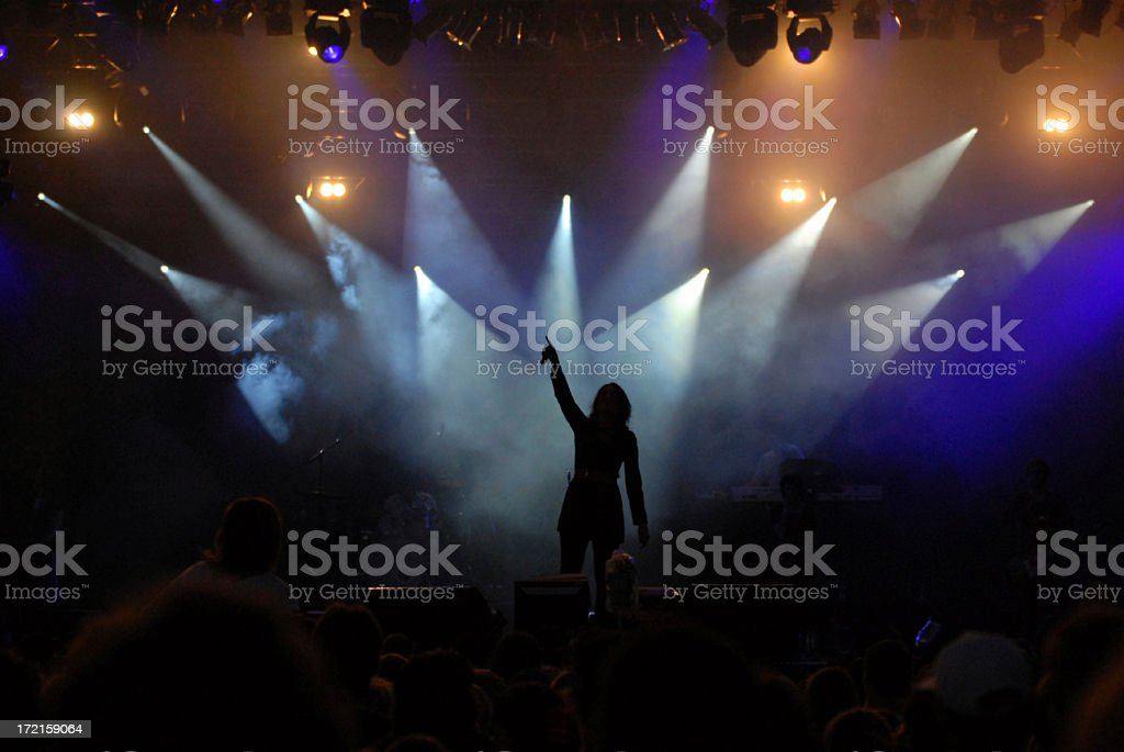 Silhouette of singer performing on stage under spotlights royalty-free stock photo