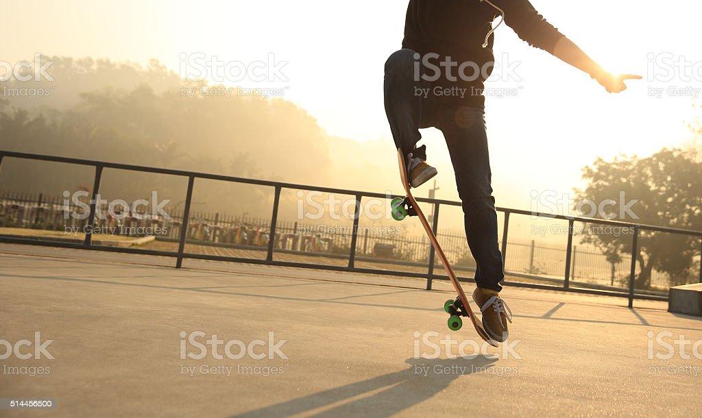 silhouette of skateboarder skateboarding at sunrise skatepark stock photo