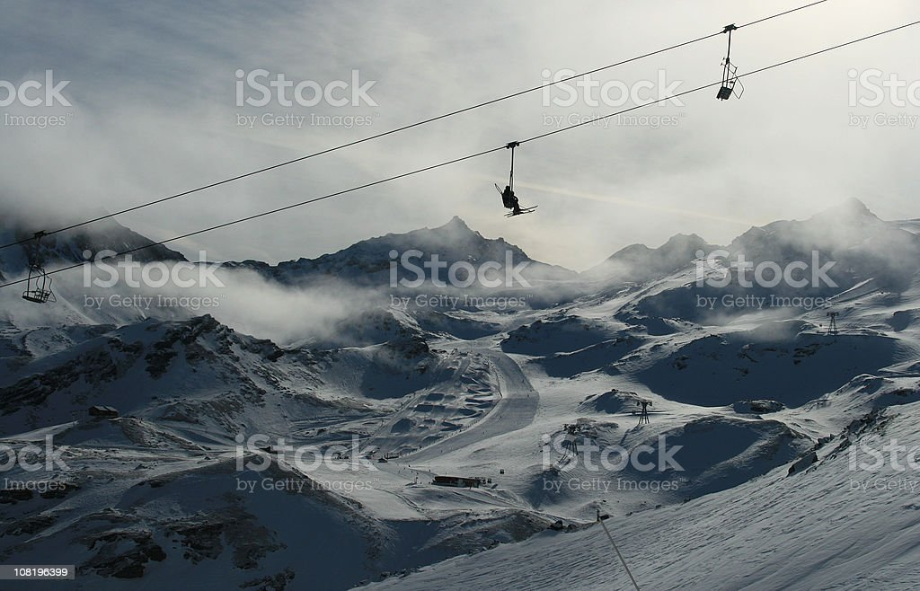 Silhouette of Ski Lift Above Snow and Trois Vallees Mountains royalty-free stock photo