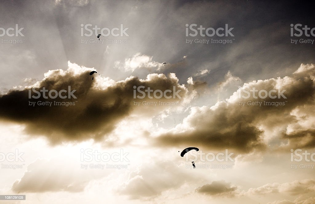 Silhouette of Skydivers on Cloudy Day in Sky royalty-free stock photo