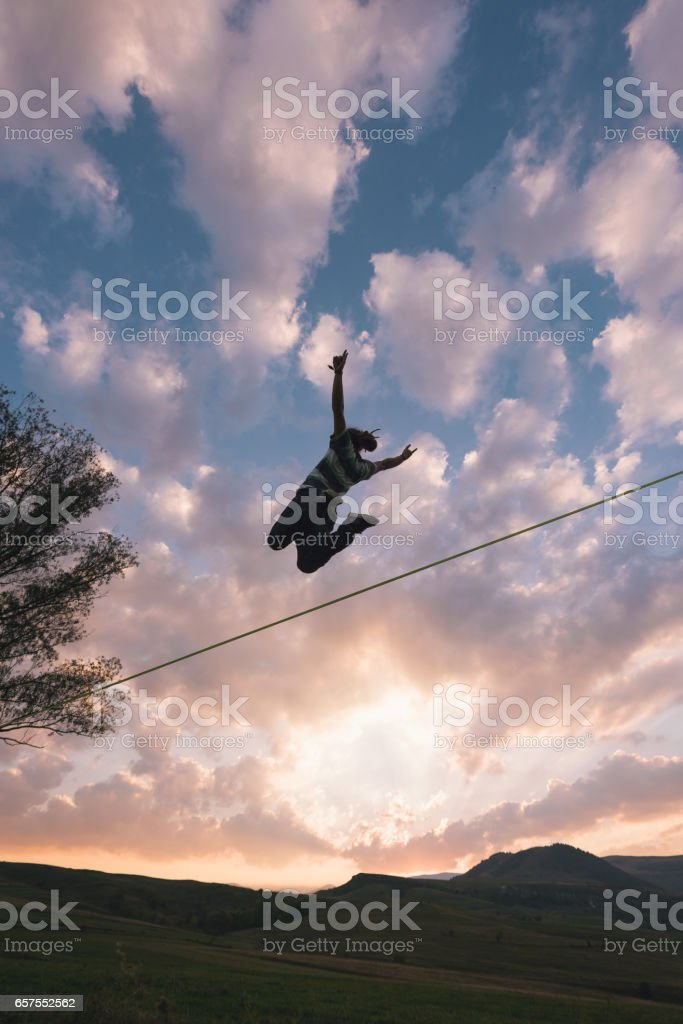 Silhouette of slackliner floating in air stock photo