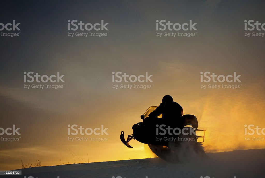 Silhouette of Snowmobile Jumping Over Snow Drift stock photo