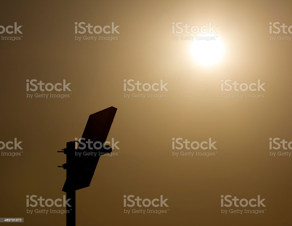 silhouette of solar panel with the Sun in background stock photo