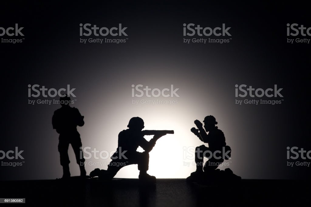 Silhouette of soldiers on a dark background. Terrorism concept. stock photo