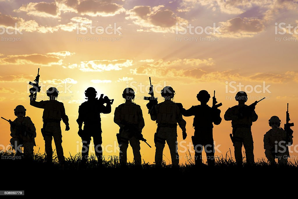 silhouette of  Soldiers team with sunrise background stock photo