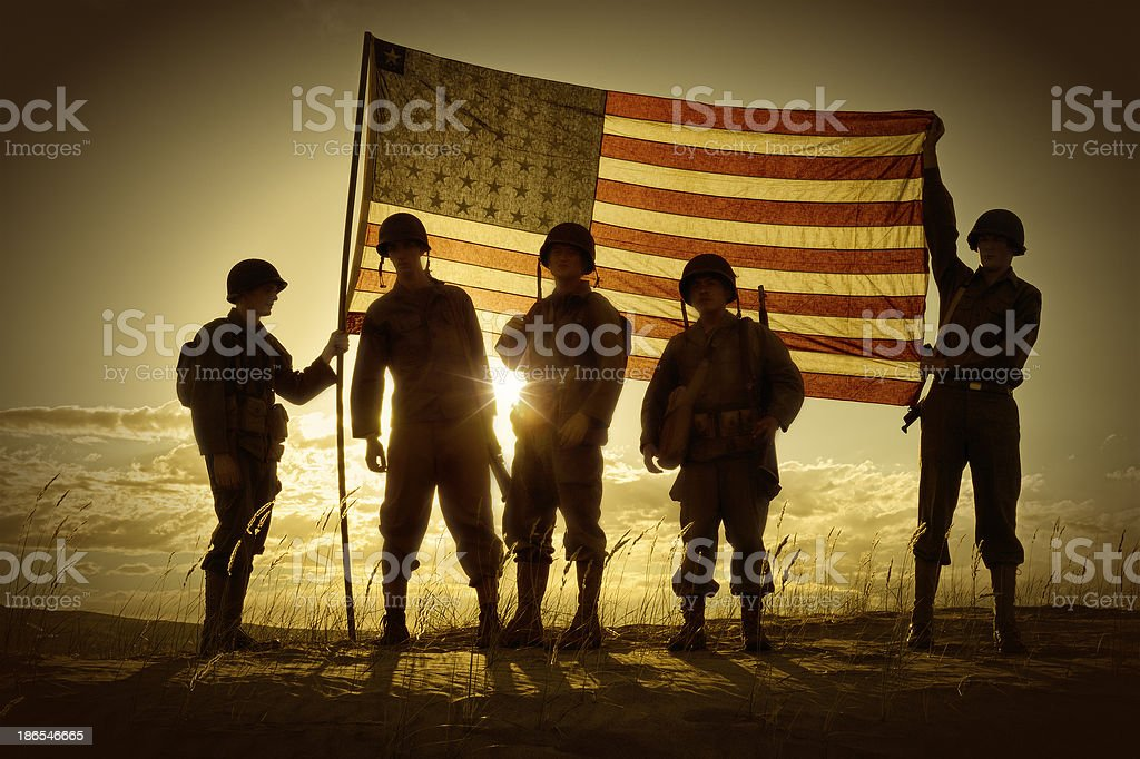Silhouette of soldiers with American flag stock photo
