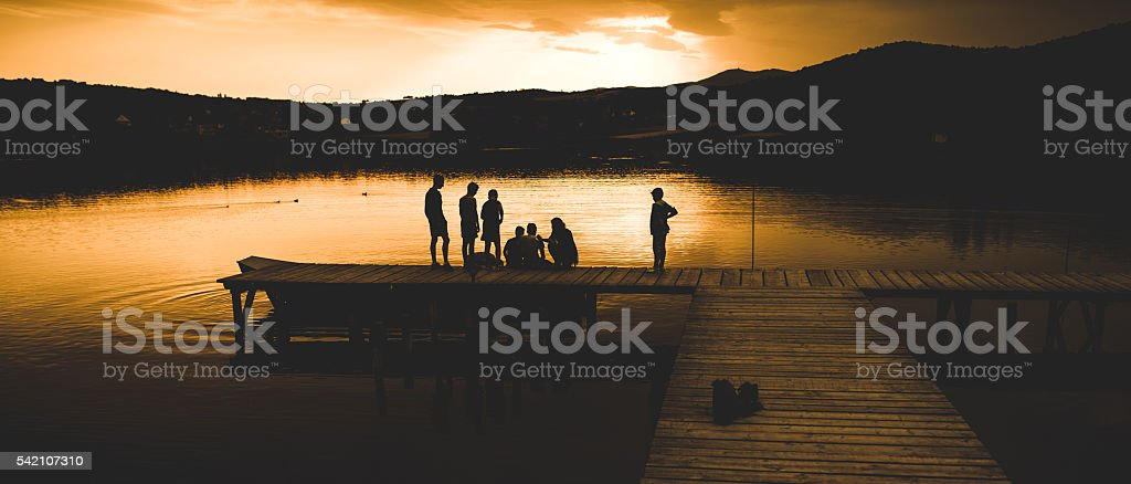 Silhouette of some kids on the lake stock photo