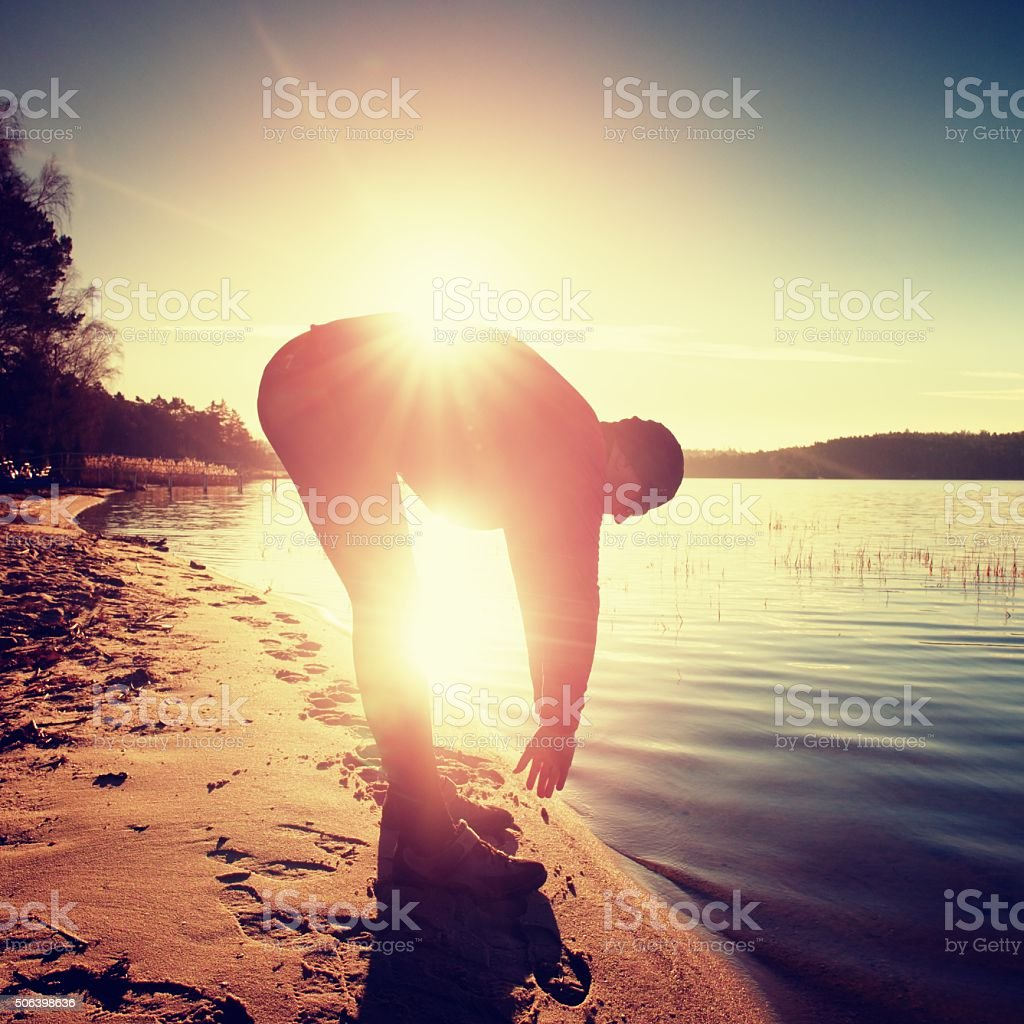 Silhouette of sport active man running and exercising on beach stock photo
