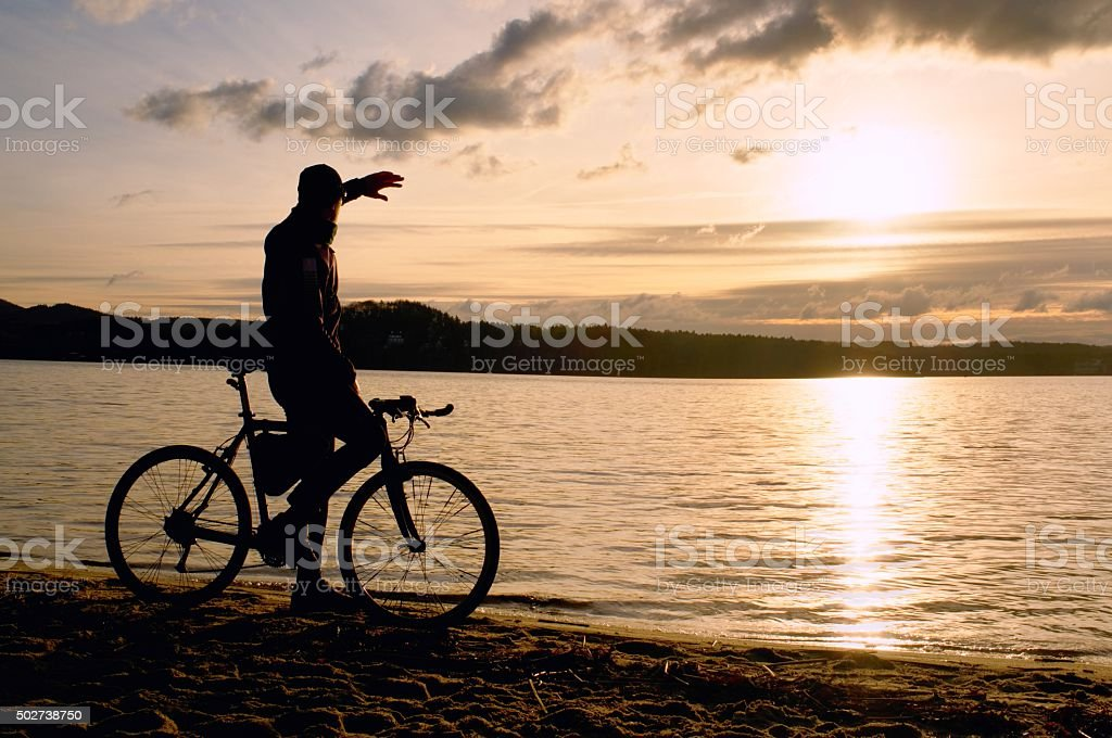 Silhouette of sportsman  holding bicycle on lake beach stock photo
