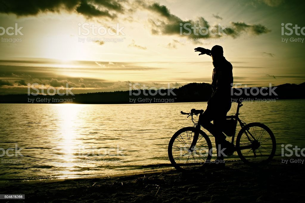 Silhouette of sportsman  holding bicycle on lake bech, colorful stock photo