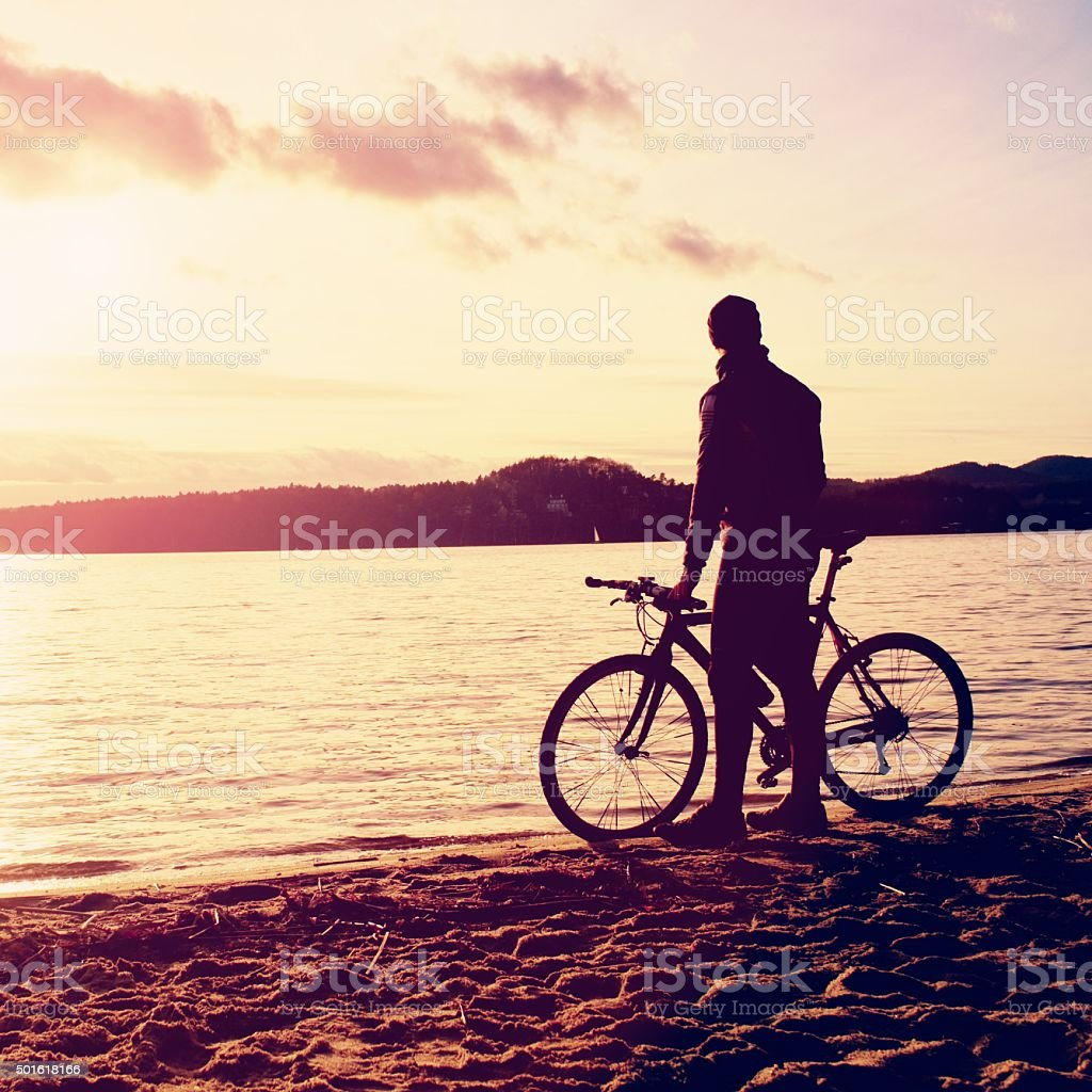 Silhouette of sportsman  holding bicycle on lake bech, colorful  sunset stock photo