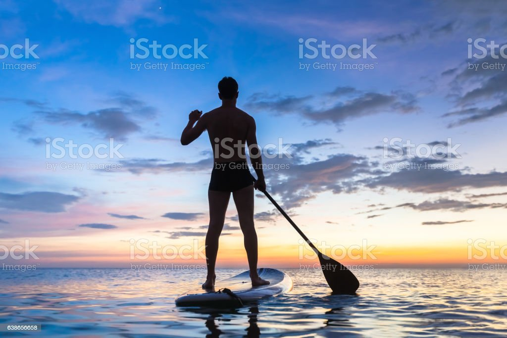 Silhouette of stand up paddle boarder paddling at sunset, sea stock photo