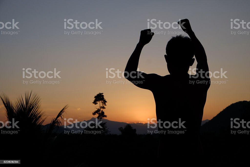 silhouette of Successful man with arm up. stock photo