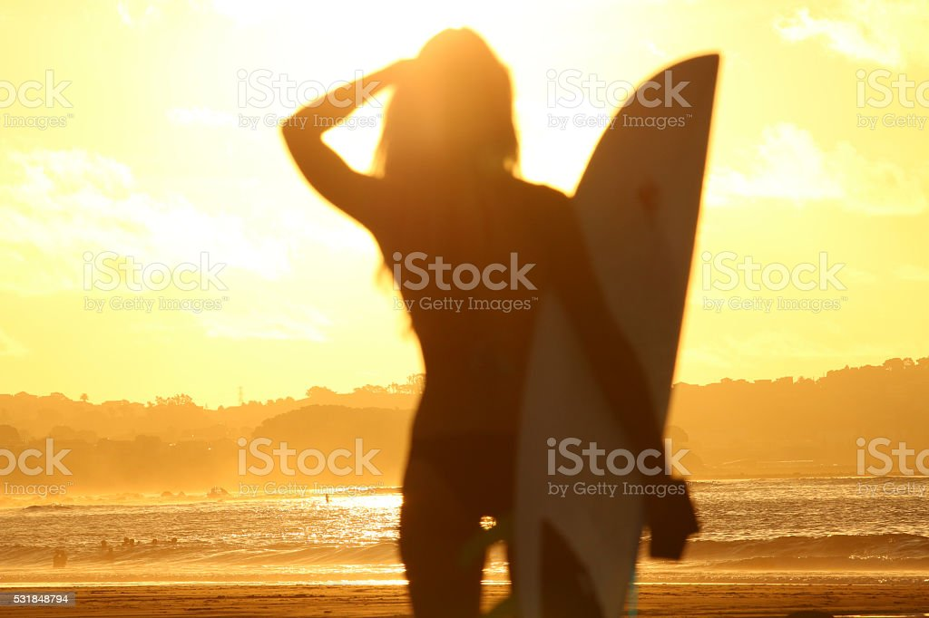 Silhouette of surfer girl at sunset stock photo