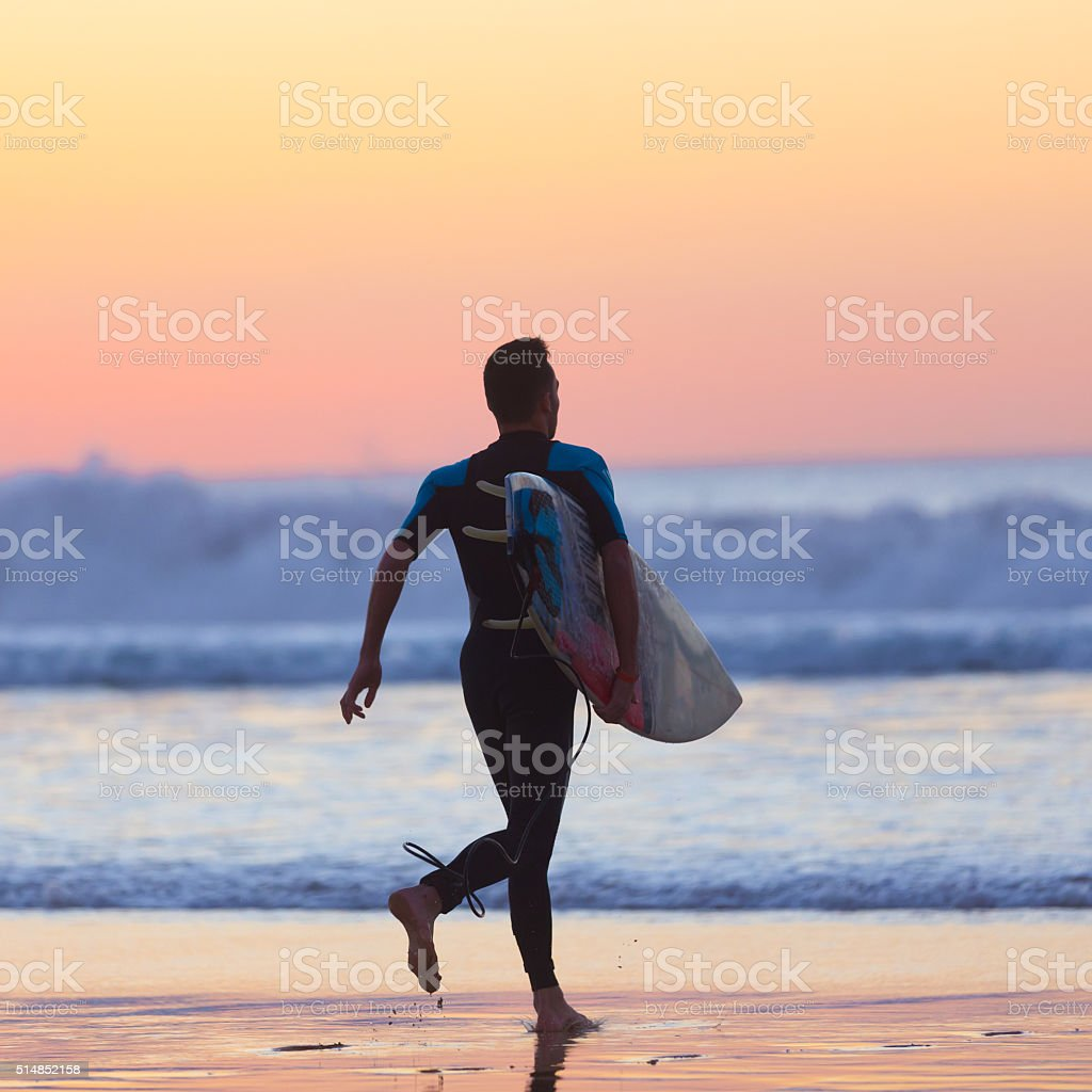Silhouette of surfer on beach with surfboard. stock photo